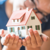 image of young woman aging out of foster care supporting a tiny house in her hands