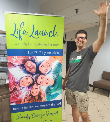 Eric Dronen standing next to a welcome sign at Life Launch Program of Finally Family Homes