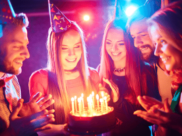 image of a young women being given a birthday cake with lit candles