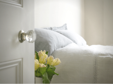 image of a white door opening to a bedroom in a host home with a bed and flowers