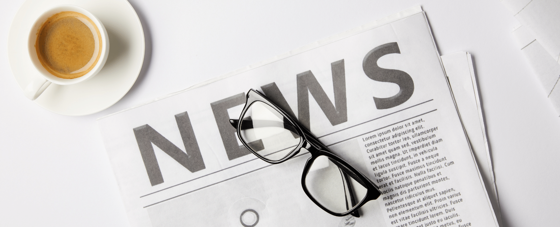 image of coffee cup filled with coffee, a news article, and dark rimmed glasses sitting on top of a white table