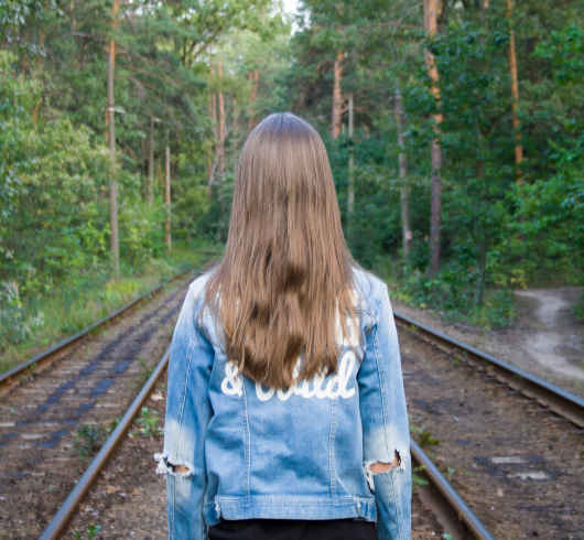 isolated young female former foster youth standing in the woods on the train tracks looking away from the camera
