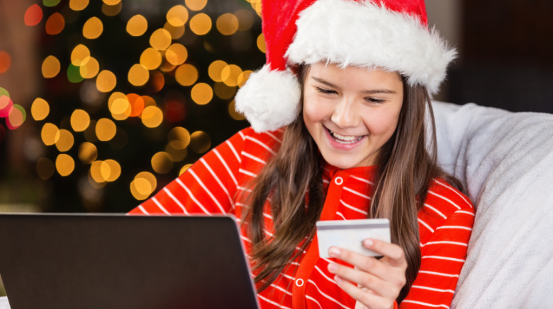 teen girl smiling while holding a credit card for kids and shopping online