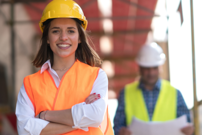 young woman in a construction hat smiling while she builds her tiny house on wheels