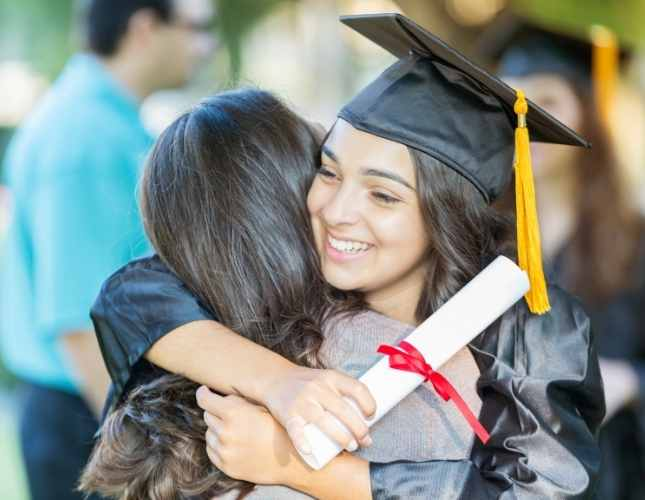 young female former foster youth college graduate hugging her supporter