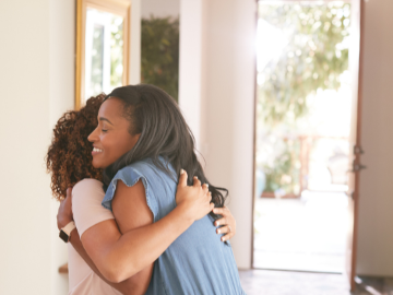 young woman coming back home to with front door open and hugging mom