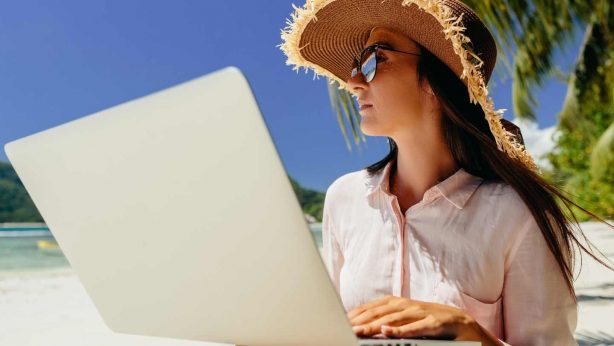 young woman in a hat working online at the beach