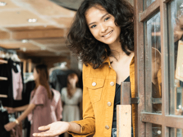 young woman opening the door with a smile
